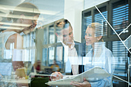 Smiling business team behind glass wall in office looking at folder - WESTF021630