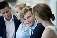 Smiling businessman looking at female colleague - WESTF021633