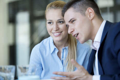 Businessman and businesswoman in office talking - WESTF021642