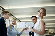 Smiing business team in office pointing at chart - WESTF021645