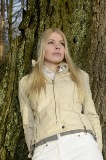 Portrait of blond woman leaning against tree trunk - BFRF001700