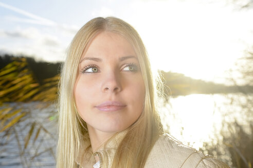 Portrait of blond woman in front of a lake at backlight - BFRF001706