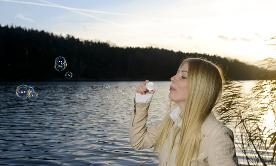 Blond young woman blowing soap bubbles in front of a lake - BFRF001709