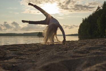Finland, Karelia, Uukuniemi, little girl turning wheel on the beach at sunset - JBF000262