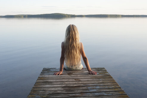 Finland, Karelia, Uukuniemi, Lake Pyhäjärvi, back view of a girl sitting on jetty - JBF000265