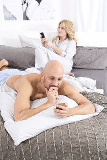 Mature couple in bedroom using their mobile phones - MAEF011078