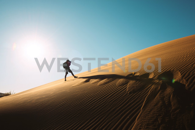 Namibia, Namib Desert, Sossusvlei, Man taking pictures on a dune at sunset - GEMF000551
