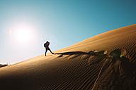 Namibia, Namib Desert, Sossusvlei, Man taking pictures on a dune at sunset - GEMF000551