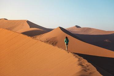 Namibia, Namib Desert, Sossusvlei, Woman walking on Dune 45 at sunrise - GEMF000557