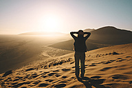 Namibia, Namib Desert, Sossusvlei, Woman enjoying sunrise on the Dune 45 - GEMF000560