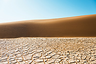 Namibia, Namib Desert, Sossusvlei, Dry cracked earth, dune and blue sky - GEMF000563