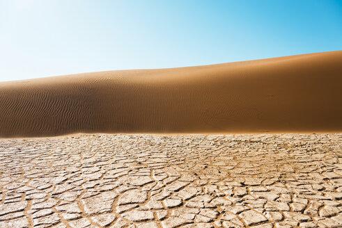 Namibia, Namib Desert, Sossusvlei, Dry cracked earth, dune and blue sky - GEMF000563