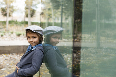 Portrait of smiling little boy and his mirror image on a glass pane - VABF000017