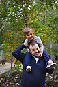 Laughing little boy sitting on his father's shoulders - VABF000020