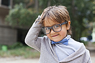 Portrait of smiling little boy with hand on his head wearing bow tie and oversized spectacles - VABF000026
