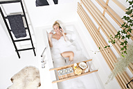 Woman on the phone in bubble bath - MAEF011103