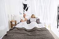 Mature couple lying in bed, having relationship problems - MAEF011112