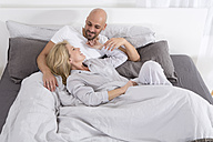 Happy couple cuddling in bed - MAEF011121