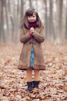 Young girl, brown coat in park, autum, smiling, hands folded - XCF000045