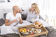 Happy couple having breakfast in bed - MAEF011135