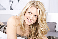 Blond woman lying in bed - MAEF011140