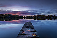 Wooden boardwalk on lake with autum leaves, morning sky - MBOF000032