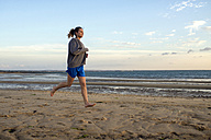 Spain, Puerto Real, young woman jogging on the beach at evening twilight - KIJF000042