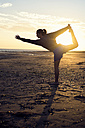 Spain, Puerto Real, silhouette of young woman doing yoga on the beach at sunset - KIJF000051