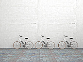 Row of three parked electric bicycles in front of concrete wall, 3D Rendering - UWF000705
