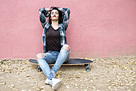 Portrait of young woman sitting on longboard relaxing in front of pink wall - KIJF000054