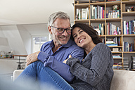 Smiling mature couple cuddling at home - RBF003639