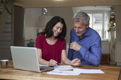 Smiling couple at home with laptop and papers at table - RBF003645