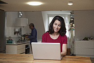 Smiling woman at home using laptop with man in background - RBF003648
