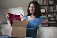 Smiling woman at home sitting on couch unpacking parcel with garment - RBF003660