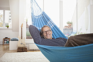 Smiling mature man at home lying in hammock - RBF003675