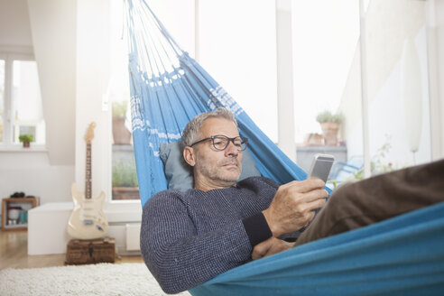 Mature man at home lying in hammock looking at cell phone - RBF003678