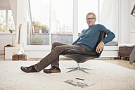 Relaxed mature man at home sitting in chair - RBF003681