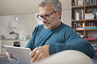 Mature man at home using digital tablet - RBF003690