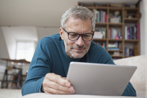 Mature man at home lying on couch using digital tablet - RBF003702