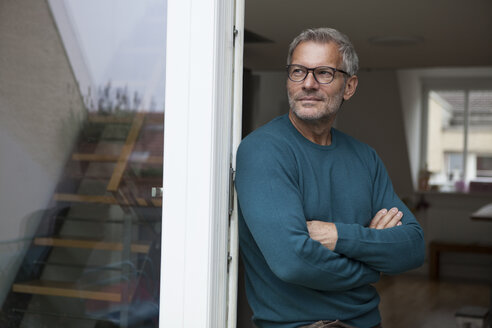 Mature man leaning against balcony door - RBF003711