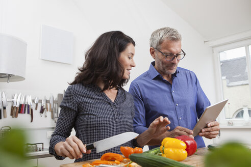 Mature couple with digital tablet cooking in kitchen - RBF003726