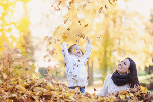 Happy girl with mother playing with autumn leaves - HAPF000059