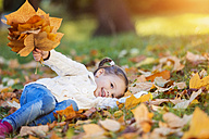 Happy girl lying in autumnal meadow - HAPF000077