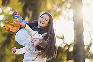 Happy mother carrying daughter holding autumn leaves - HAPF000080