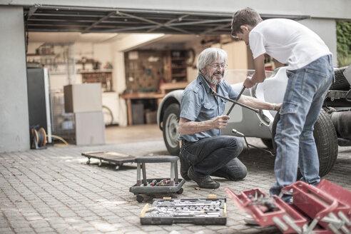 Grandfather and grandson restoring a car together - ZEF007636