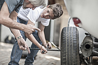 Grandfather and grandson changing car tire - ZEF007639