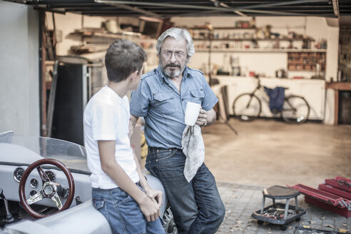 Grandfather and grandson having a break from restoring a car - ZEF007645