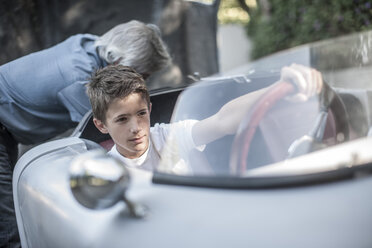 Boy sitting in sports car with grandfather in background - ZEF007648