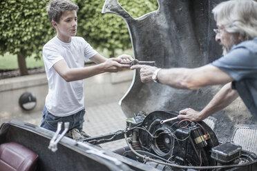 Grandfather and grandson restoring a car together - ZEF007651