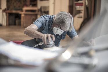 Senior man restoring a car - ZEF007663